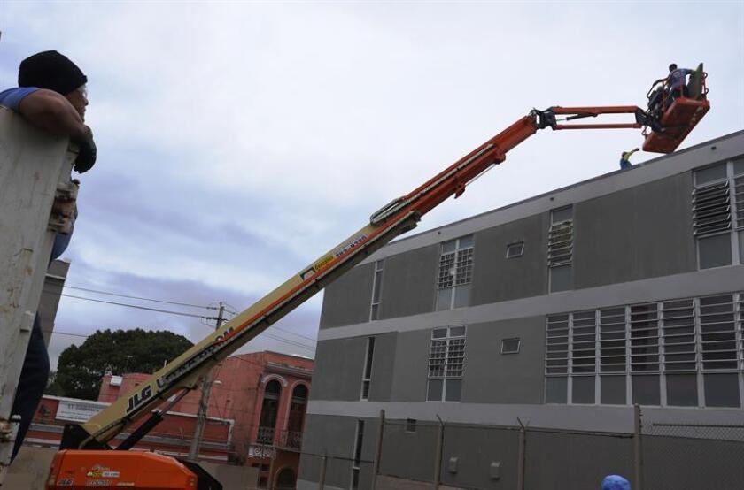 Unas personas subidas a una grúa aseguran el techo de un edificio en San Juan (Puerto Rico). EFE/Archivo
