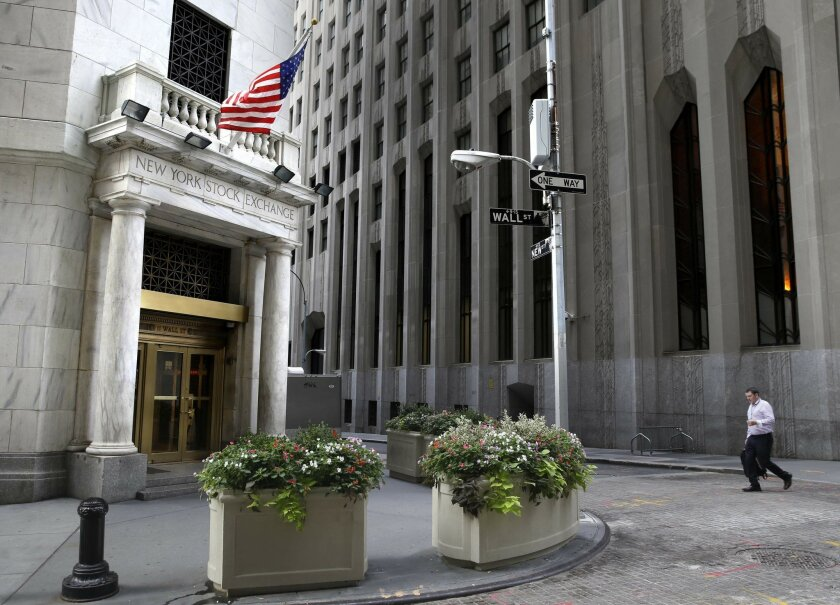 FILE - In this Monday, Aug. 24, 2015, file photo, a man walks towards the New York Stock Exchange. Weak Chinese economic data weighed on global stocks Monday, May 16, 2016, at the start of a week that's likely to be dominated by speculation over whether the U.S. Federal Reserve will raise interest