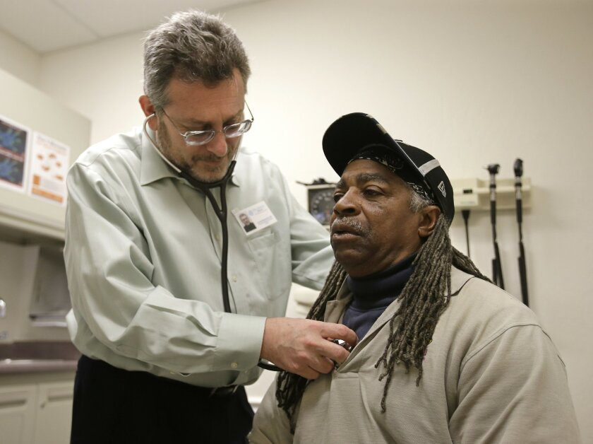 In this photo taken Thursday, Feb. 18, 2016 Doctor Leonid Basovich, left, examines Medi-Cal patient Michael Epps, at the WellSpace Health clinic in Sacramento, Calif. California lawmakers are considering a tax package that would appease federal health insurance regulators and close a $1.1 billion budget gap. Both chambers of the California Legislature are expected to vote Monday, Feb. 29, 2016, on bills that would adjust taxes on health insurance plans. (AP Photo/Rich Pedroncelli)