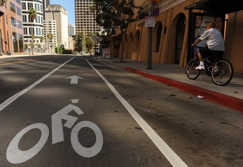 A man rides on the sidewalk despite the new commuter bike lane on 7th Street in downtown Los Angeles.