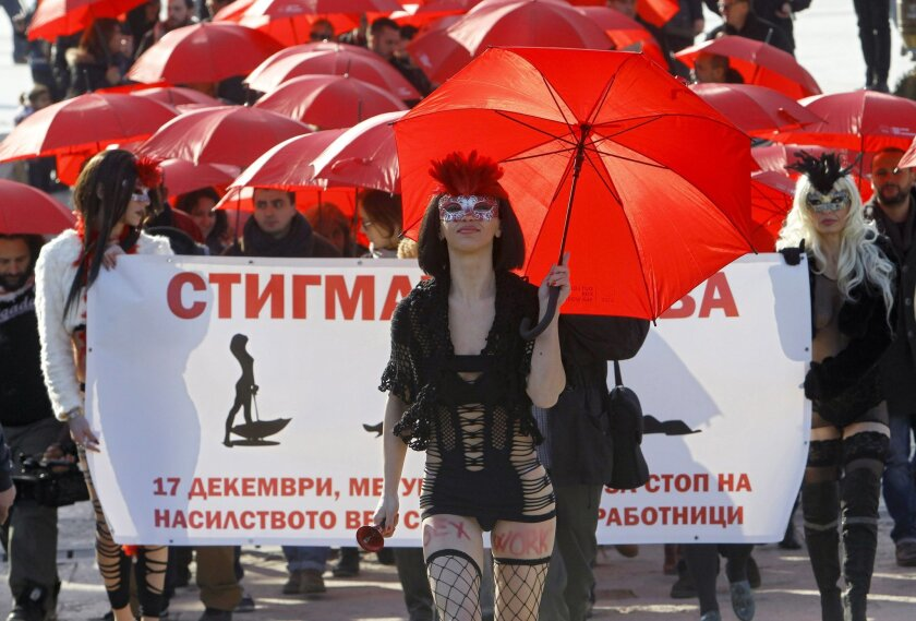 People carrying red umbrellas march through downtown Skopje, Macedonia, marking the International Day to End Violence against Sex Workers, Thursday, Dec. 17, 2015. A group of sex workers, supported by members of non-government organizations, rallied Thursday demanding rights for the sex workers and destigmatization of their profession. The banner reads: The Stigma Kills. (AP Photo/Boris Grdanoski)