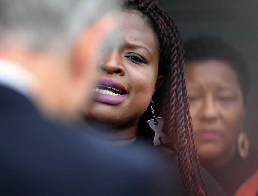 Minneapolis NAACP President Nekima Levy-Pounds, center, speaks against police brutality during a press conference following U.S. Attorney Andrew Luger's announcement that no criminal civil rights charges will be filed against two white Minneapolis police officers in the November shooting death of J