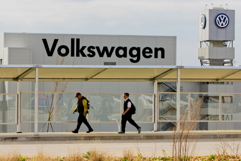 Workers walk by the Volkswagen plant in Chattanooga, Tenn.