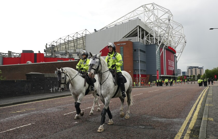 Police officers on horseback patrol outside the Old Trafford stadium in Manchester, England, Tuesday, May 11, 2021 ahead of the English Premier League soccer match between Manchester United and Leicester City. This is the first Manchester United home match since fans protested against American owner Joel Glazer, forcing the postponement of the team's Premier League game against Liverpool. The protests prompted Glazer to publish a letter in which he pledged to accelerate discussions with fans about supporters being able to have a greater say at the club. (AP Photo/Jon Super)