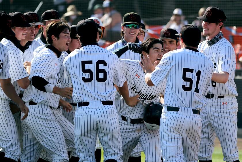 Caden Aoki of Huntington Beach High baseball, center, celebrates with teammates after hitting a home run against Edison.
