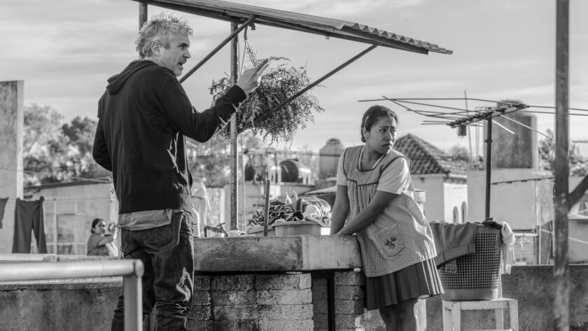 This image released by Netflix shows filmmaker Alfonso Cuaron, left, and Yalitza Aparicio on the set