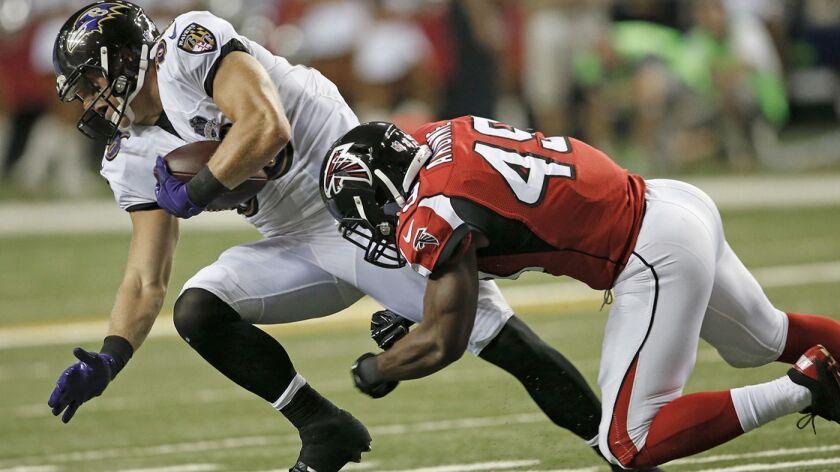 Baltimore tight end Konrad Reuland makes a catch in front of Atlanta linebacker Derek Akunne on Sept