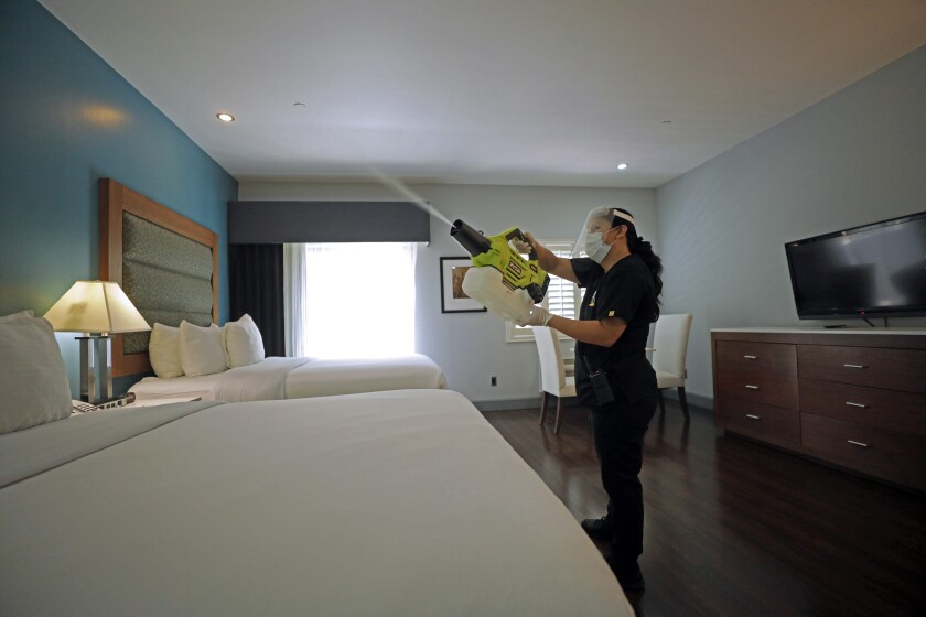 A worker at a hotel in Studio City uses a handheld machine to spray a disinfectant fog made of ethanol and hydrogen peroxide.