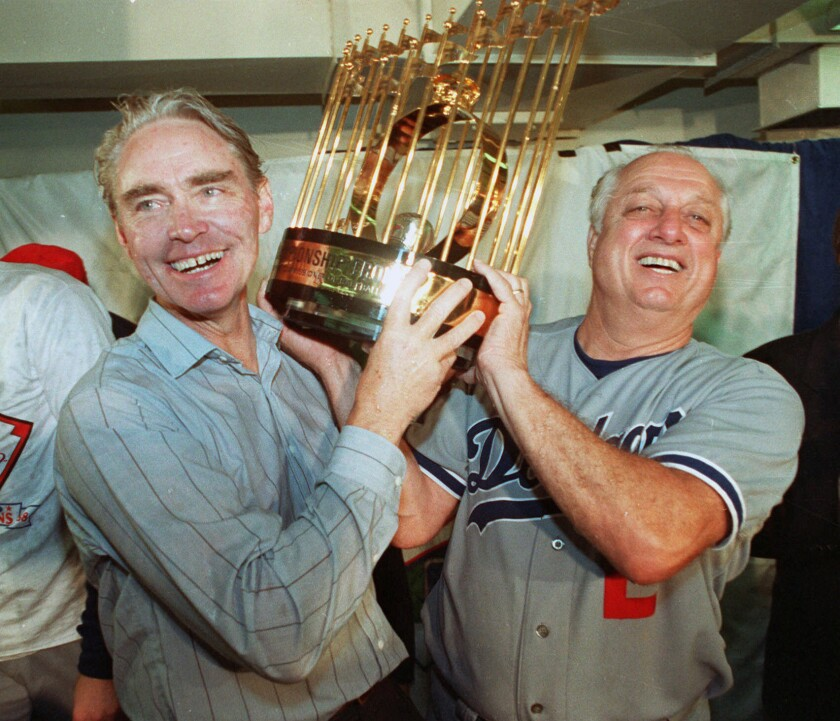 Fred Claire, Dodgers vice president, and Lasorda hoist the World Series trophy after their team's 1988 victory.