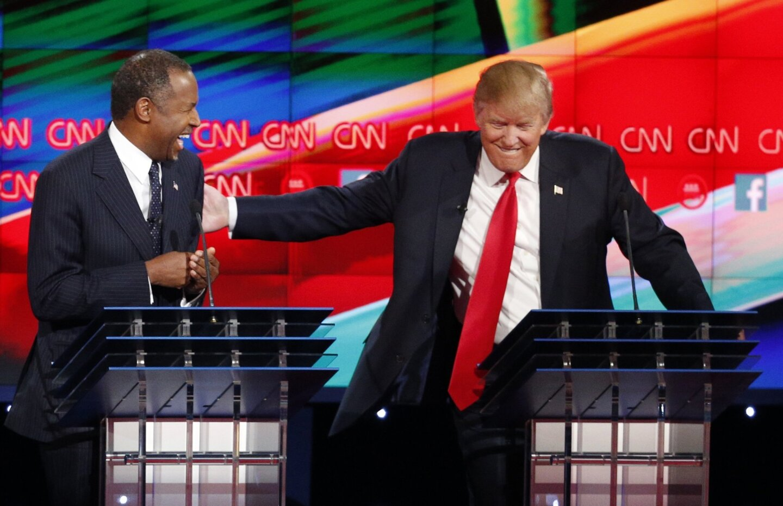 Ben Carson, left, and Donald Trump laugh during the Republican presidential debate at the Venetian Hotel & Casino in Las Vegas.