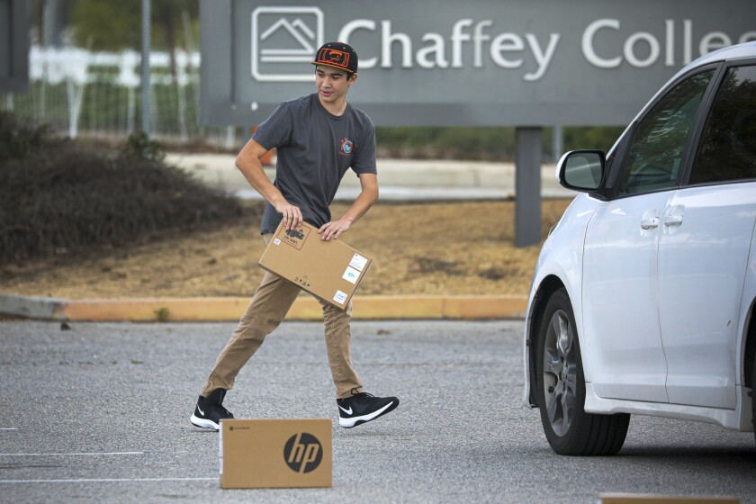 Following social distancing measures, a student picks up a laptop placed in a parking lot.