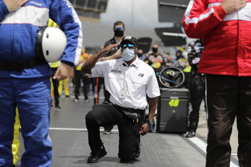 A NASCAR official kneels during the national anthem before a NASCAR Cup Series auto race at Atlanta Motor Speedway.