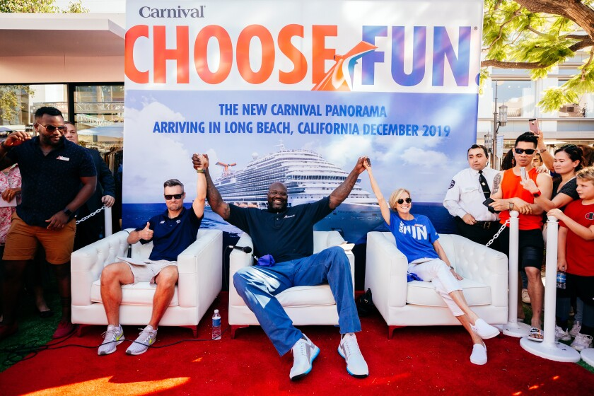 Shaquille O'Neal, center, has some fun during a Carnival Cruises event at the Grove in Los Angeles last year. After all, he's the cruise line's chief fun officer.