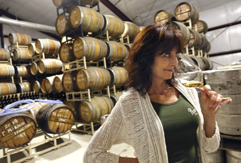 Lola Glossner, owner of Pendray's Distillery in Templeton, Calif., just south of Paso Robles, checks the aroma from a glass of nebbiolo brandy inside the storage warehouse.