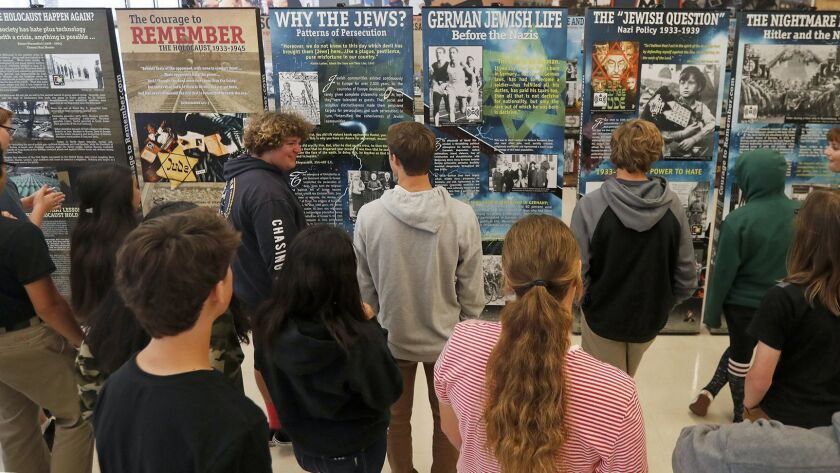 """Ninth-graders from teacher Jillian Jontig's English class view the exhibit """"The Courage to Remember: The Holocaust 1933-1945"""" at Huntington Beach High School on Monday. The exhibit features more than 200 photos."""
