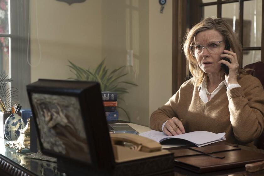 डेस्क पर बैठी महिला टेलीफोन पर बात करती है
