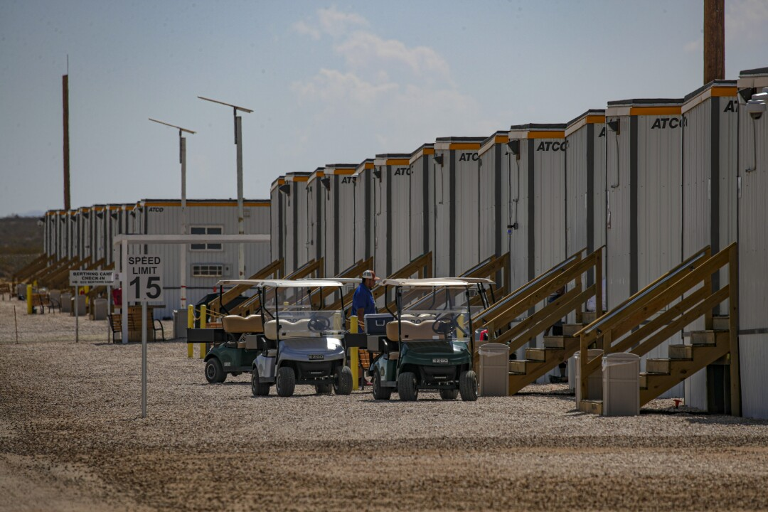 Golf carts are parked along a line of trailers