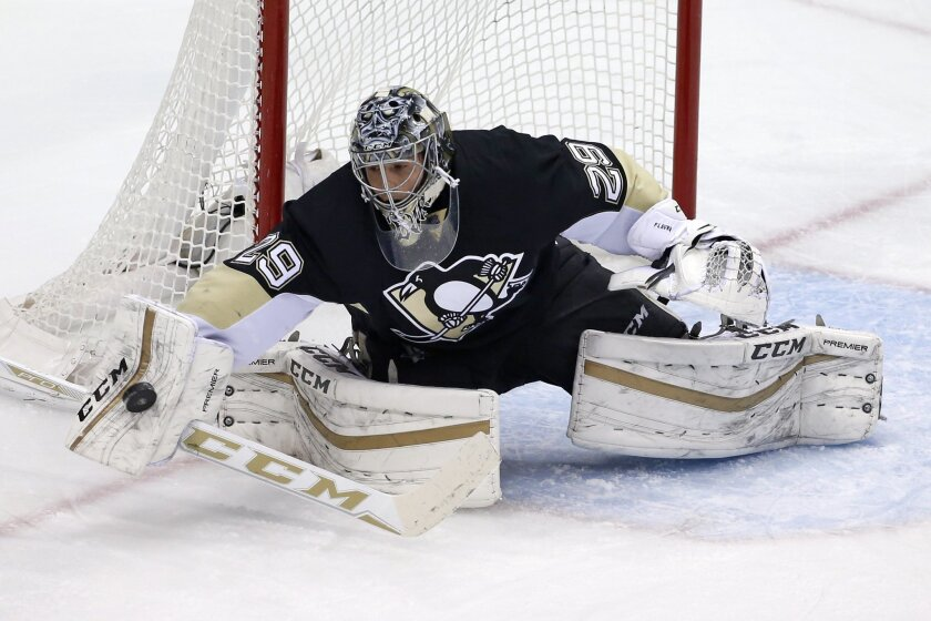 Pittsburgh Penguins goalie Marc-Andre Fleury (29) blocks a shot during the first period of an NHL hockey game against the Detroit Red Wings in Pittsburgh, Thursday, Feb. 18, 2016. (AP Photo/Gene J. Puskar)
