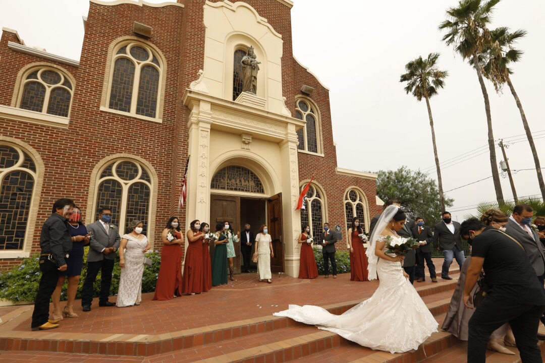 Masked guests attend a wedding at Our Lady of Guadalupe Catholic Church in Mission, Texas.