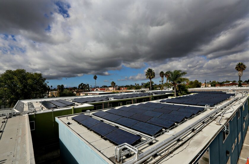 Banks of Solar panels sit atop and apartment building along 34th Street in the Normal Heights section of San Diego on Wednesday, November 20, 2013.(Photo by Sandy Huffaker)