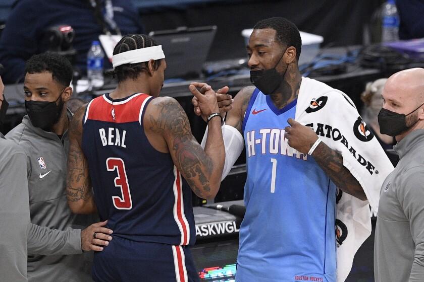 Houston Rockets guard John Wall (1) and Washington Wizards guard Bradley Beal (3) meet up after an NBA basketball game, Monday, Feb. 15, 2021, in Washington. The Wizards won 131-119. (AP Photo/Nick Wass)