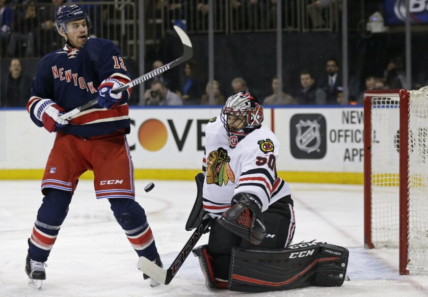 Chicago Blackhawks goalie Corey Crawford (50) makes a save as New York Rangers left wing Daniel Paille (12) looks to knock down the puck during the second period of an NHL hockey game Wednesday, Feb. 17, 2016, in New York. (AP Photo/Adam Hunger)