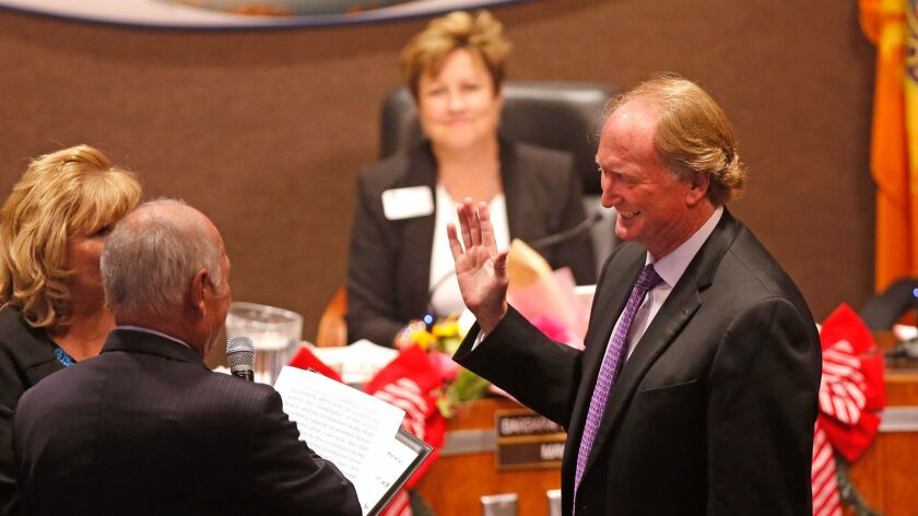 Mike Posey, who had been mayor pro tem, is sworn in as Huntington Beach mayor on Monday night as outgoing mayor Barbara Delgleize looks on.