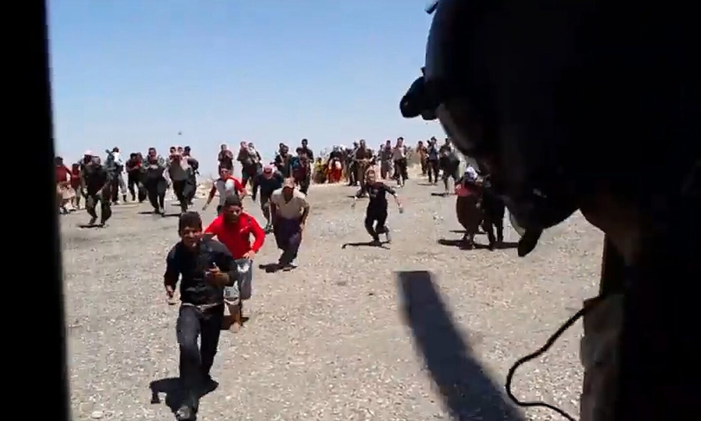 An image from a video by Austrian politician Michel Reimon shows Iraqi refugees racing to board an Iraqi helicopter aid flight in the north of the country.