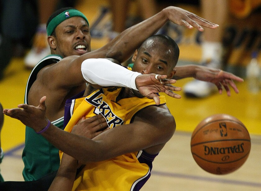 Celtics forward Paul Pierce forces Lakers guard Kobe Bryant to make a pass while driving to the basket.