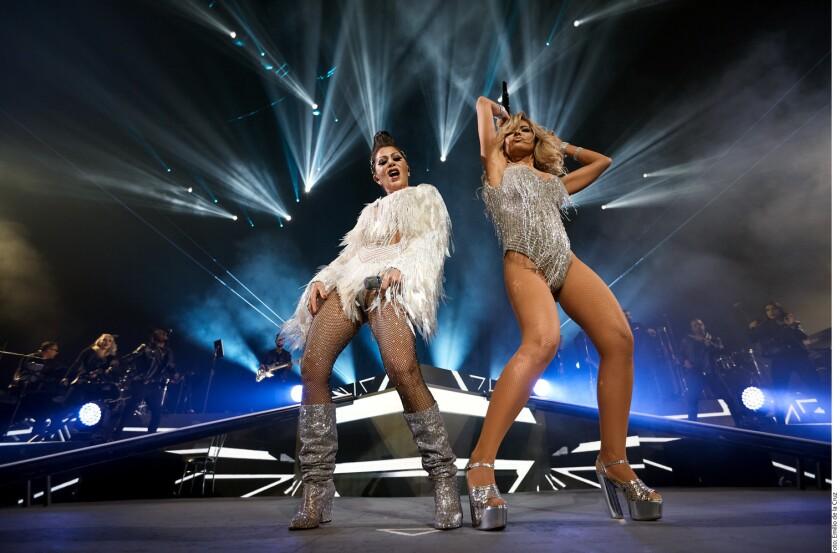 """Con ambas en escena, en vestidos claros brillantes, Alejandra Guzmán y Gloria Trevi salieron de en medio del escenario para interpretar """"Más buena"""", una de sus colaboraciones."""