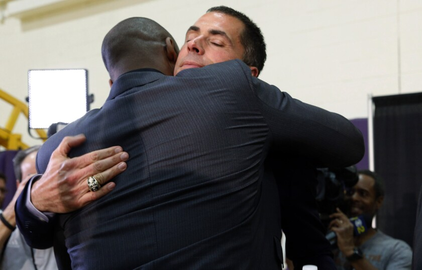Kobe Bryant, left, hugs Rob Pelinka, at a news conference in El Segundo March 10, 2017.