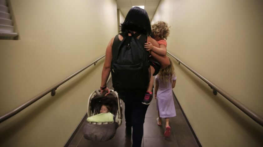 A mother takes her children to their room at the San Fernando Valley Rescue Mission last November. More than 11% of Los Angeles County families on welfare assistance are homeless, according to state statistics.