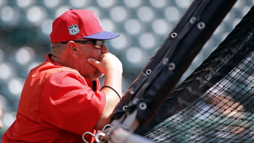 Philadelphia Phillies coach Matt Stairs watches batting practice before a spring training baseball g