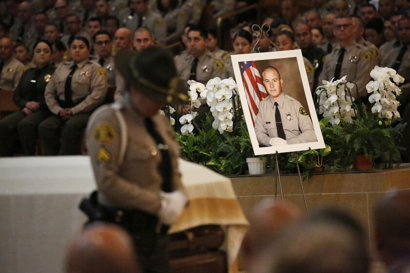 LOS ANGELES, CA - JUNE 24, 2019 - A portrait sits next to the casket of Los Angeles County Sheriff's