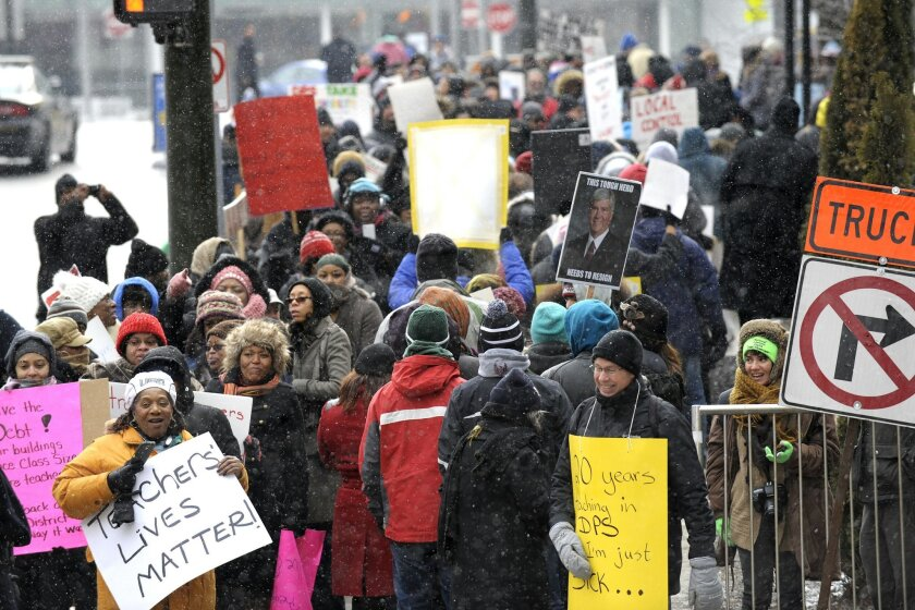 Burton International Academy computer advanced teacher Denice McGee, bottom left, holds a sign as she and other protesters wait to cross the street Wednesday, Jan. 20, 2016, in Detroit. Most of Detroit's public schools closed for the day on Wednesday due to teacher absences, as disgruntled educators stepped up efforts to protest the governor's plans for the district, its ramshackle finances and dilapidated buildings. (Todd McInturf/Detroit News via AP) DETROIT FREE PRESS OUT; HUFFINGTON POST OUT; MANDATORY CREDIT
