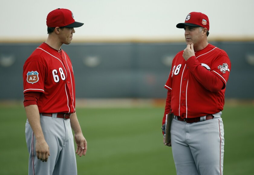Cincinnati Reds manager Bryan Price talks to Kyle Skipworth during a spring training baseball workout Thursday, Feb. 18, 2016, in Goodyear, Ariz. (AP Photo/Morry Gash)