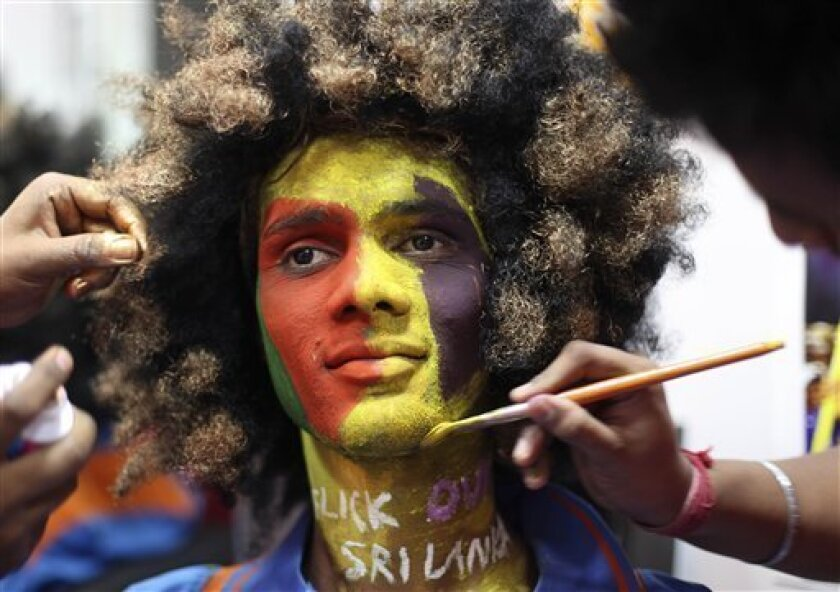 Indian artists paint the face of a cricket fan, ahead of the ICC World Cup cricket final match between India and Sri Lanka, in Mumbai, India, Friday, April 1, 2011. (AP Photo/Rafiq Maqbool).