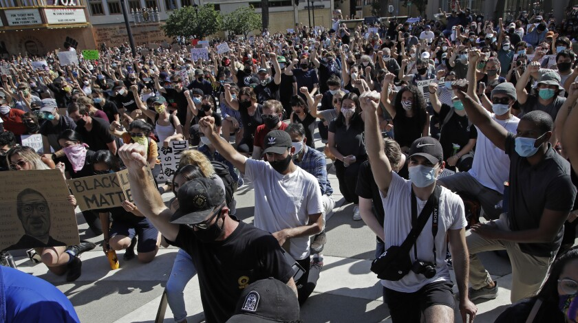 People raise a fist as they take a knee during a protest Tuesday, June 2, 2020, in Redwood City, Calif. (AP Photo/Ben Margot)