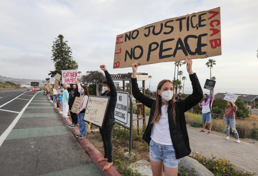 Sophia Wheeler, 13, holds her message for passing traffic along S. Coast Highway 101 at the Cardiff Kook statue on Wednesday.