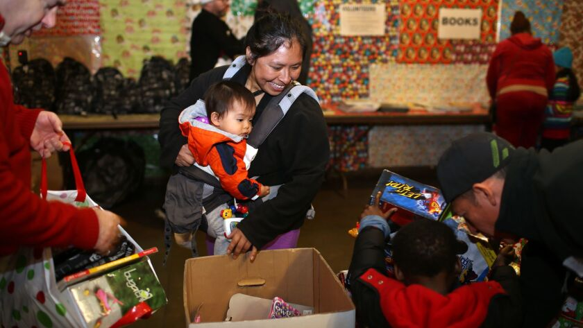 Zarela Lopez carries her one year old baby Liesel Shanell Lopez through a room full of toys to pick up four to take home.