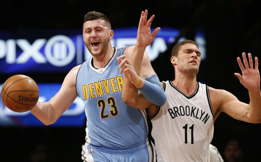 Denver Nuggets center Jusuf Nurkic (23) gets his arm tangled up with Brooklyn Nets center Brook Lopez (11) as he drives down court in the first half of an NBA basketball game, Monday, Feb. 8, 2016, in New York. (AP Photo/Kathy Willens)