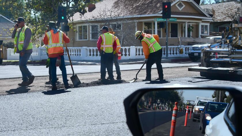 Workers repave a road in South Pasadena.