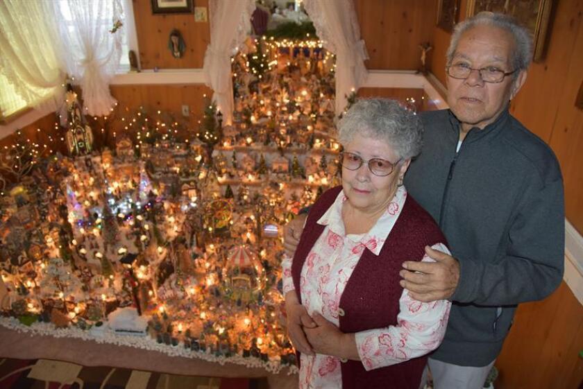 """Enedina Amezquita y su esposo, Alfonso, posan frente al pesebre de su casa en Lynwood (California), que atrae desde hoy a cientos de celebrantes de las posadas al niño Dios. """"Me gusta comprar estos juguetes, porque me gusta jugar, al hacer mi nacimiento yo juego"""", dijo a Efe Amezquita, de 76 años y originaria de Jalisco (México), quien lleva desde el año 1978 elaborando un pesebre en su hogar, iluminado y bastante cargado de figuras tradicionales de la Navidad. EFE"""