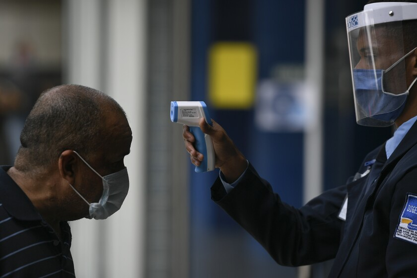 A man gets his temperature taken as a measure to curb the spread of the new coronavirus, at the entrance of El Recreo mall in Caracas, Venezuela, Wednesday, June 17, 2020. (AP Photo/Matias Delacroix)