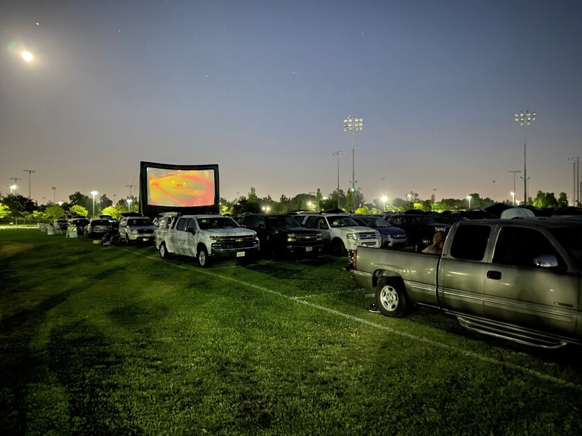 Cars park on the grass at Mile Square Park in Fountain Valley to watch a drive-in movie s on Aug. 1.