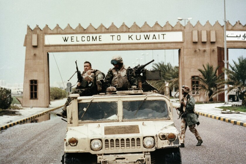 """FILE - In this Wednesday February 27, 1991 file photo, members of Task Force Ripper of the First Marine Division ride a Humvee under a """"Welcome to Kuwait"""" sign at the entrance to Kuwait City's International Airport. In February 1991, after months of building an international coalition, U.S. forces entered Kuwait to end the Iraqi occupation of its smaller, oil-rich neighbor. (AP Photo/Patrick Downs, File)"""