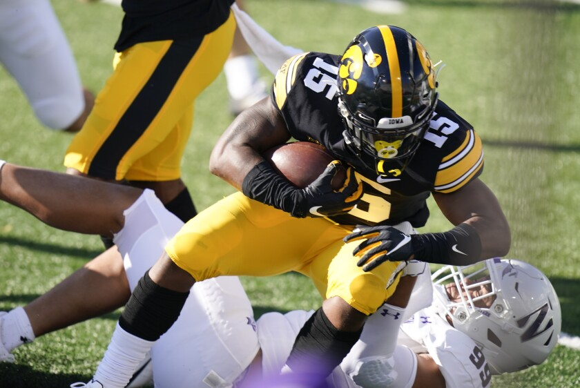 Iowa running back Tyler Goodson (15) is tackled by Northwestern defensive end Earnest Brown IV during the first half of an NCAA college football game, Saturday, Oct. 31, 2020, in Iowa City, Iowa. (AP Photo/Charlie Neibergall)