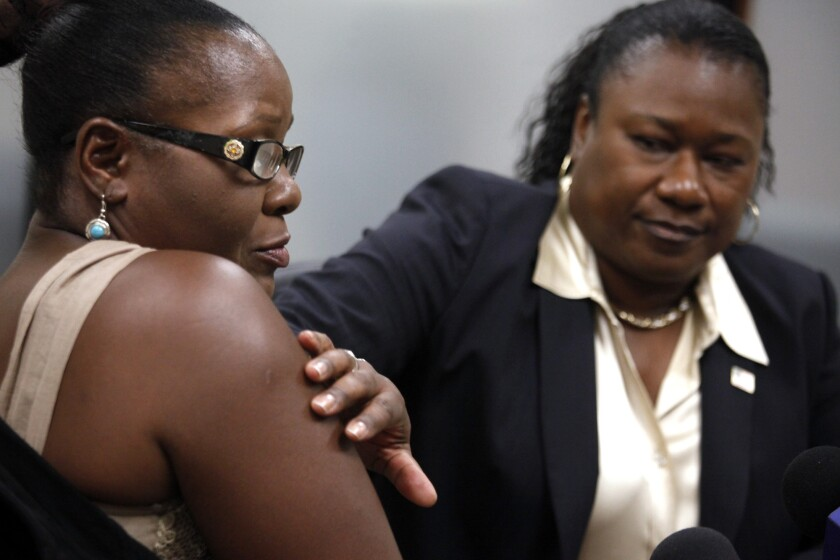 Attorney Caree Harper, right, runs her hand over a lump that's visible on Marlene Pinnock's arm that they said came from a beating by a CHP officer in August.