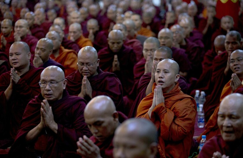 In this June 27, 2013 photo, controversial Buddhist monk Wirathu, second right foreground, who is accused of instigating sectarian violence between Buddhists and Muslims through his sermons, performs Buddhist rituals with Myanmar's powerful Buddhist clergy in outskirts of Yangon, Myanmar. As the pr