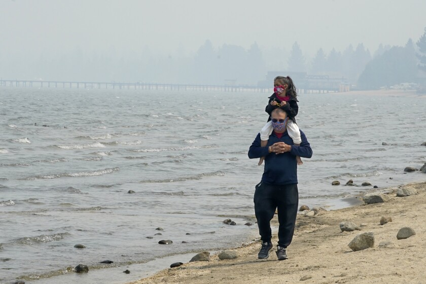 Against the backdrop of a smoky sky, a man carries a girl, both wearing face coverings, on his shoulders at Lake Tahoe.